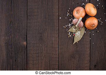 Onions, garlic and spices on an old wooden table.