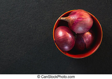Onions in a bowl on black background