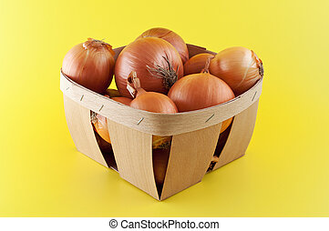 Onions in a box on yellow background.