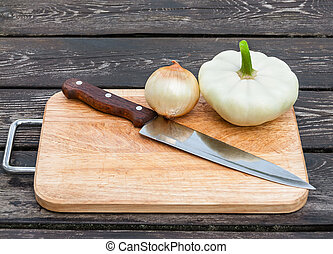 Onions, squash and knife on board