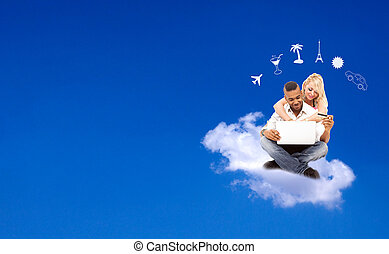 Young couple floating on a cloud booking their holidays, e-commerce concept