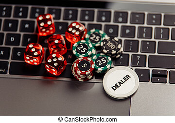 Online casino concept. Gambling chips and dices on laptop keyboard