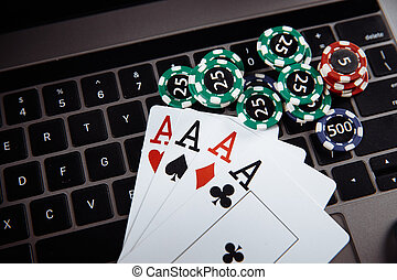 Online casino concept. Gambling chips and playing cards on laptop keyboard
