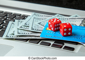 Online casino, online gambling. Money cash dollars and credit brief with dice for gaming on laptop keyboard.
