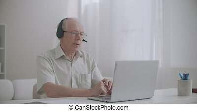 online consultation with lawyer, retiree man is helping people, chatting online with client, working from home, using laptop with internet