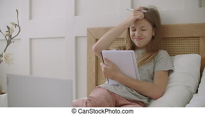 online education for schoolchildren, girl is learning from home, sitting on bed with laptop, holding copybook and pen for lesson, portrait of teen female