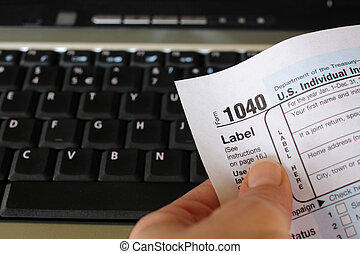 Online filing - A person holds a Income Tax form in front of...