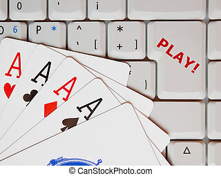 Poker aces and computer keypad with enter key replaced with text Play! as a concept of on-line gaming