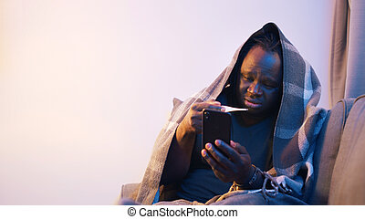 Online health care. Sick man wrapped in blanket measuring temperature and seeking distance medical help