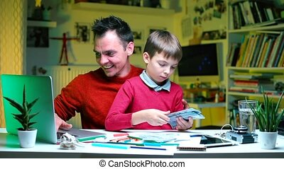 Online learning businessman sitting at a table with a child talking to viewer.