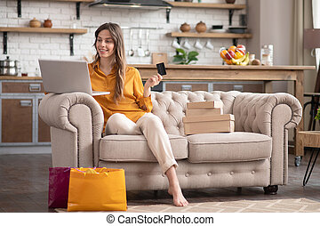 Long-haired girl in a mustard color blouse sitting on the sofa with a laptop