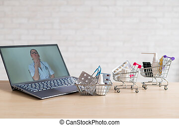Online medicine and pharmacy concept. A female doctor conducts an online consultation and recommends medications. Mini trolley with tablets at the laptop.