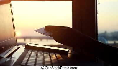 Online mobile payment method using mobile smart phone and credit card. Close up of woman is shopping on her laptop in blurred city background during amazing sunset. 3840x2160