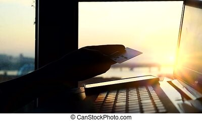 Online mobile payment method using mobile smart phone and credit card. Close up of woman is shopping on her laptop in blurred city background during sunset with lense flare effects. 3840x2160