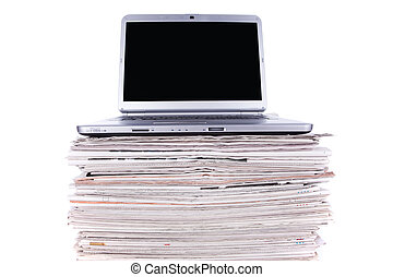 Online News - Laptop over a stack of newspapers for internet...