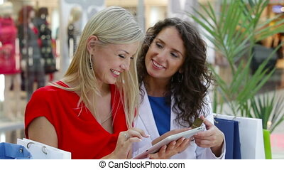 Online order - Smiling ladies making an online order while...