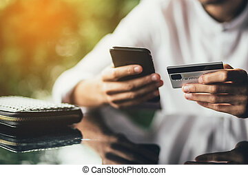 Online payment and shopping concept. male holding cell phone in one hand and credit card in other, making transaction, suing mobile banking app during lunch at cafe. Sunshine background