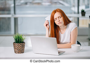 Thinking business woman sitting at table with laptop, holding empty credit card