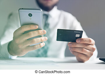 Online payments through the phone. Online trading on the currency exchange. Young businessman with a bank credit card in his hands. Smartphone and Internet Commerce. Payment of goods online.