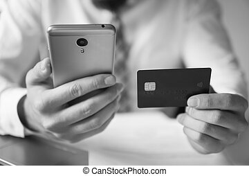 Online payments through the phone. Smartphone and Internet Commerce. Online trading on the currency exchange. Young businessman with a bank credit card in his hands. Payment of goods online.