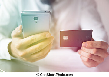 Online payments through the phone. Young businessman with a bank credit card in his hands. Online trading on the currency exchange. Payment of goods online. Smartphone and Internet Commerce.