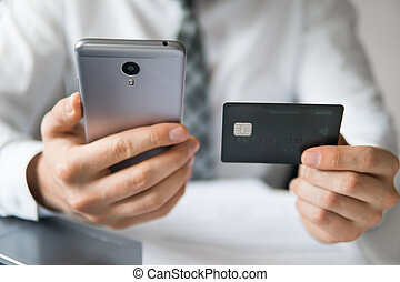Online payments through the phone. Young businessman with a bank credit card in his hands. Payment of goods online. Online trading on the currency exchange. Smartphone and Internet Commerce.