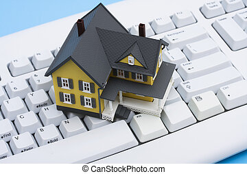 Online Real Estate - Model house sitting on a white keyboard