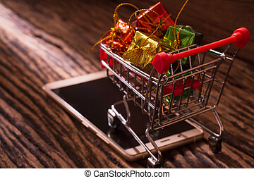 Online shopping and internet e-commerce concept. Trolley for supermarket and mobile phone on wood.