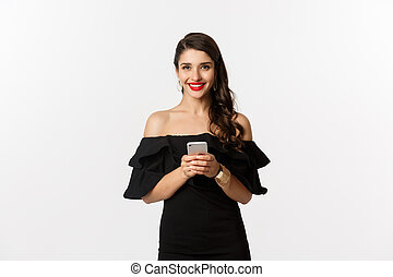 Online shopping concept. Attractive young woman in black dress, reading text message, using mobile phone and smiling, standing over white background