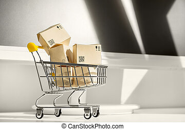 Online shopping concept. Small shopping cart with many paper boxes on the desktop. Black friday sale. Buy in one click