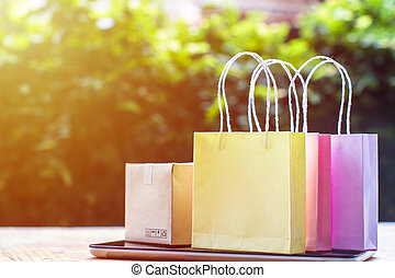 Online shopping, E-commerce, fast and easy trading concept : Colorful shopping bags, Paper carton on tablet depicts customers order things from retailer sites via the internet. Copy space for text.