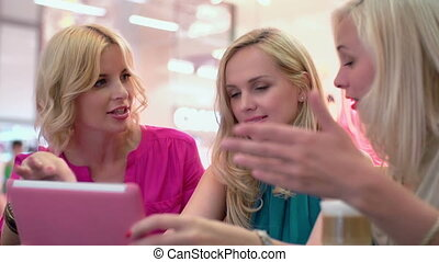 Online Store - Three friends shopping online sitting at...