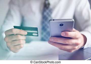 Online trading on the currency exchange. Smartphone and Internet Commerce. Payment of goods online. Online payments through the phone. Young businessman with a bank credit card in his hands.