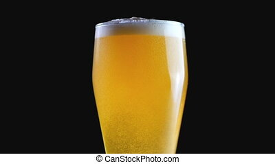 Only boiled amber beer. Beer on a black background. Bubbles and foam in a glass of beer. Slow motion