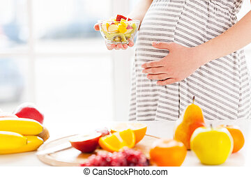 Only fresh and healthy food for my baby. Cropped image of pregnant woman holding a plate wirh fruit salad