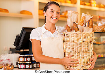 Only fresh bread for our customers. Beautiful young woman in apron holding basket with bread and smiling while standing in bakery shop