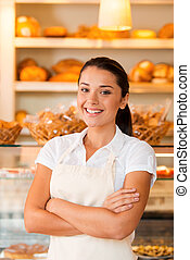 Only fresh pastry for our customers. Beautiful young woman in apron keeping arms crossed while standing in bakery shop