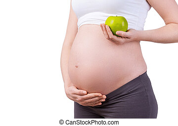 Only healthy food. Cropped image of pregnant woman holding green apple while standing isolated on white