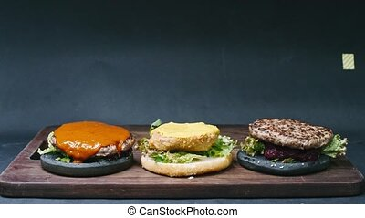?ooking tho black burgers and one cheeseburger on a black background in 4k resolution time-lapse