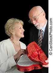 Oooooh - Chocolates! - A handsome senior man giving a...