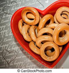 ?op, vista., rosquillas de pan, en, placa roja, en forma, de, corazón, en, gris, fondo.