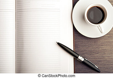 Open a blank white notebook, pen and coffee on the desk - ...