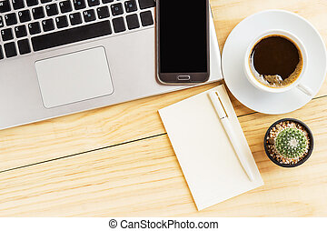 white notebook with pen,smart phone, laptop and a cup of coffee on wooden table