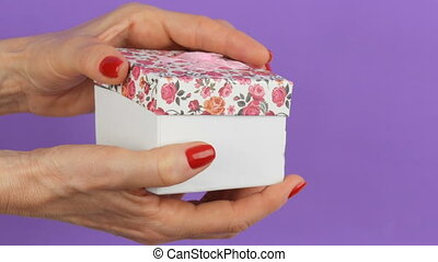 Open a small gift box with a floral print and a pink bow...