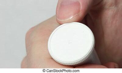 Open a vial - Hand opens a white vial
