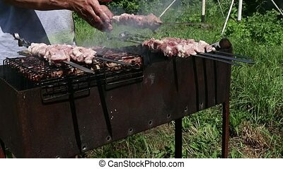 Open-air barbecue, juicy meat on the grill. hot coals and...