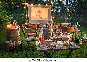 Open air cinema with retro projector in summer garden