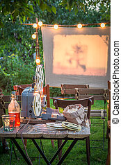 Open-air cinema with retro projector in the garden