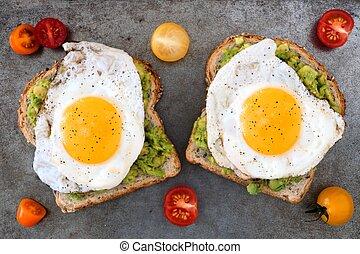 Open avocado, egg sandwiches on whole grain bread with...