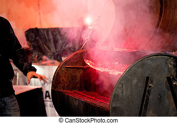Open barbeque grill with smoke coming out and red light